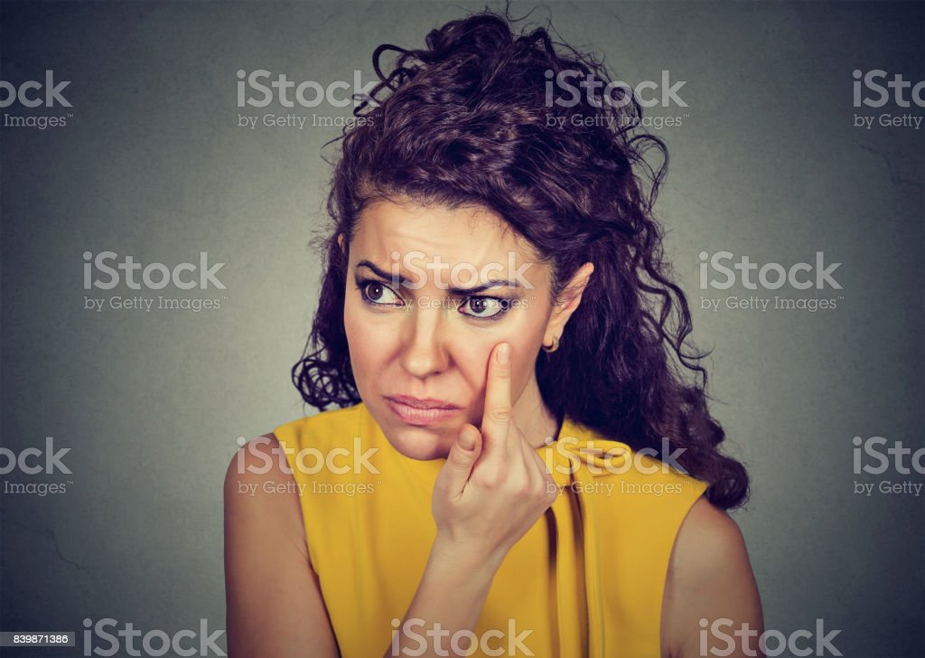 woman pulling down eyelid checking her eye looking in morrow feels unwell has black circles stock photo
