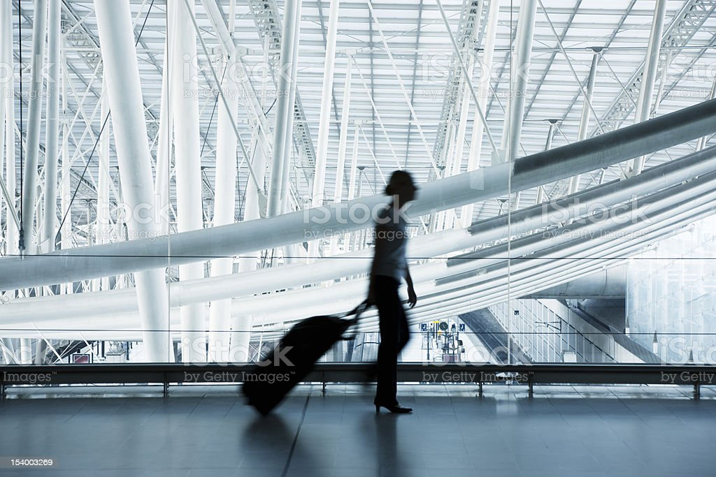 Woman Pulling Luggage at Airport, Blurred Motion, Blue Toned Image stock photo