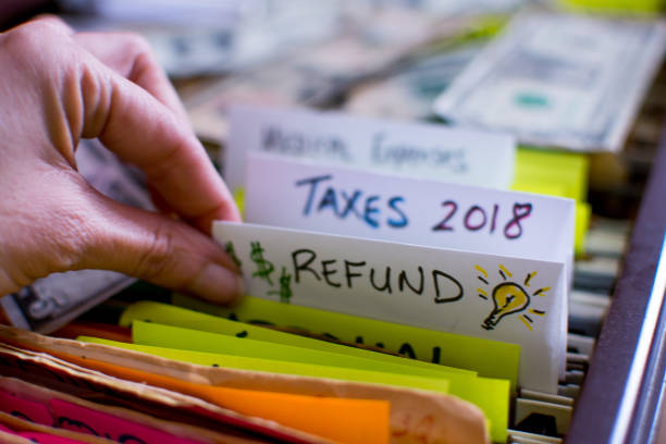 Woman pulling out file on Tax season 2018 Tax refund Hand pulling out file in filing cabinet with tax forms and papers with words Refund and Taxes 2018 handwritten on file folder conceptual dollar signs images and light bulb for ideas on tax refund conceptual financial planning photography refund stock pictures, royalty-free photos & images