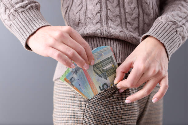 Woman pulling out lot of euros in cash from her pocket closeup stock photo