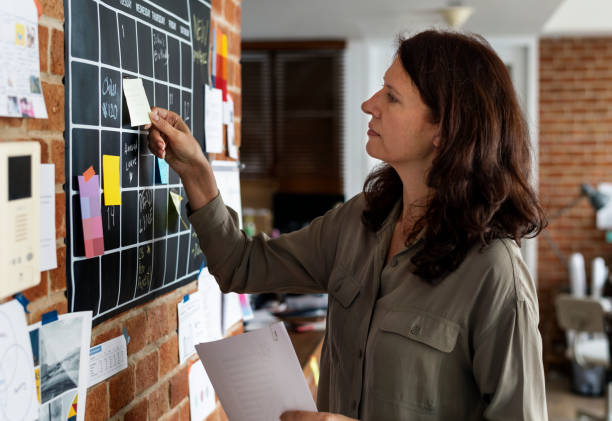 Woman pulling sticky note Woman pulling sticky note chores stock pictures, royalty-free photos & images