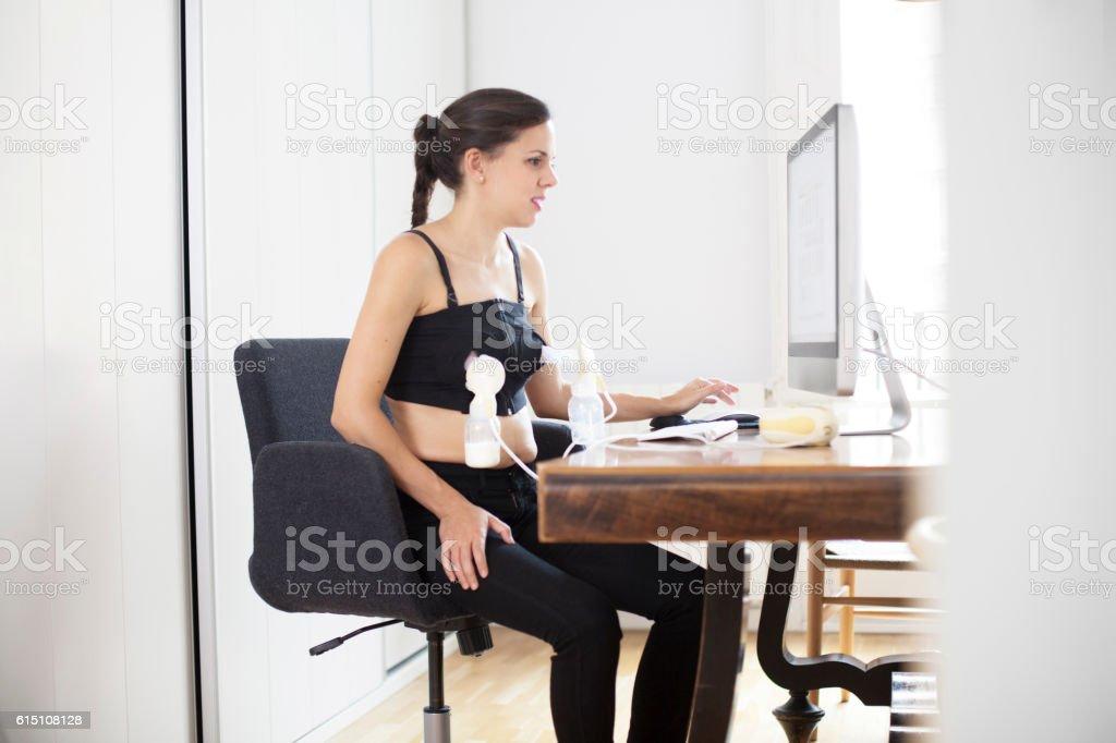 Woman pumping breast milk at work stock photo