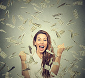 woman pumping fists celebrates success under money rain