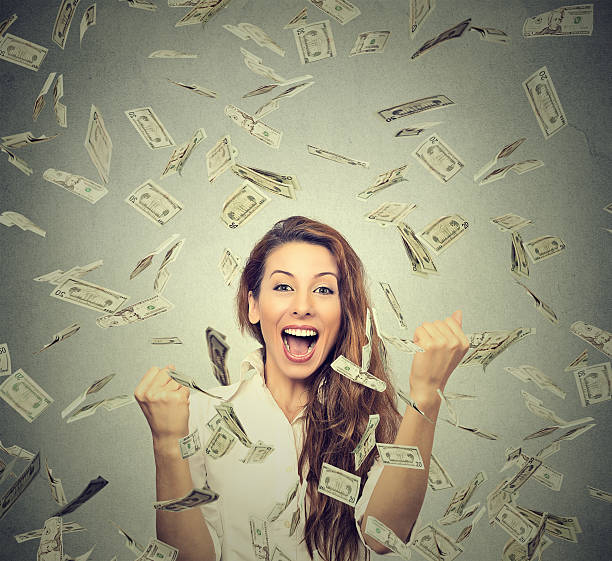 woman pumping fists celebrates success under money rain Portrait happy woman exults pumping fists ecstatic celebrates success under a money rain falling down dollar bills banknotes isolated on gray wall background with copy space millionnaire stock pictures, royalty-free photos & images