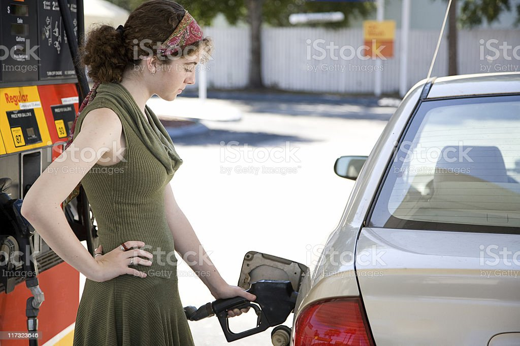 Woman pumping gas at gas station stock photo