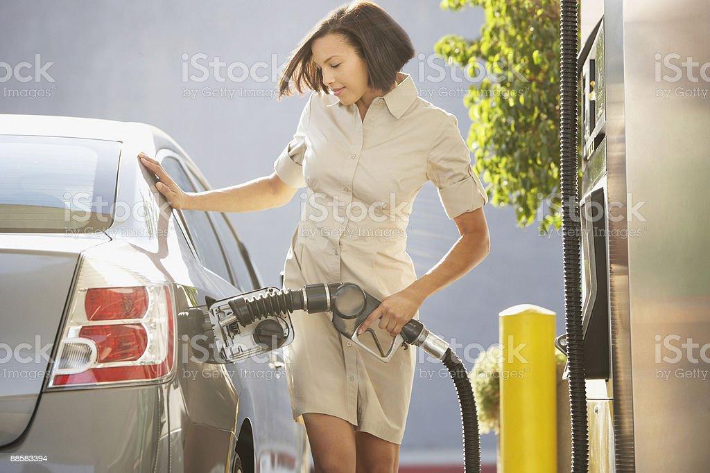 Woman pumping gas royalty-free stock photo