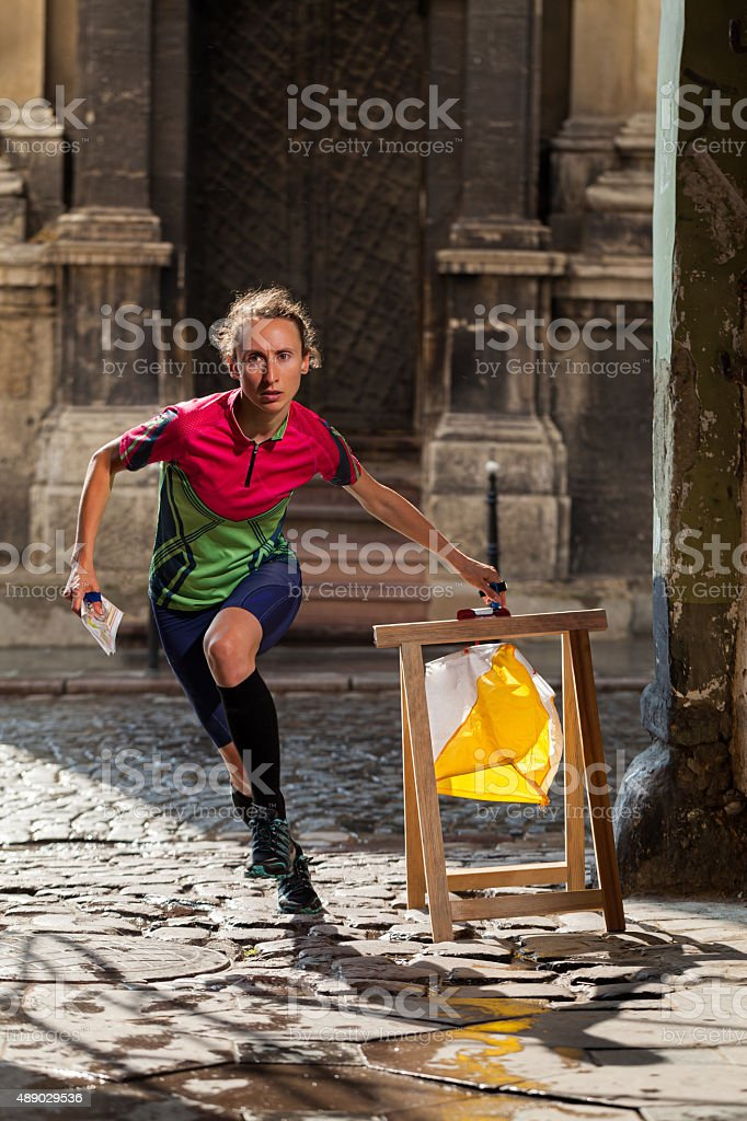 Woman punching at control point participating in orienteering competitions stock photo