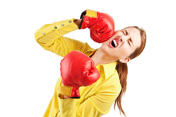 Woman Punching Herself In The Face A woman wearing boxing gloves and punching herself in the face. low self esteem stock pictures, royalty-free photos & images