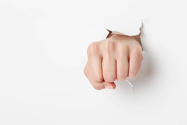 Woman punching through white paper stock photo