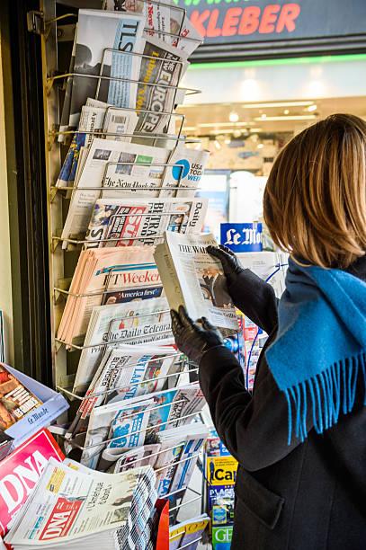 woman purchases a wall street journal newspaper from a newsstand - donald trump us president стоковые фото и изображения