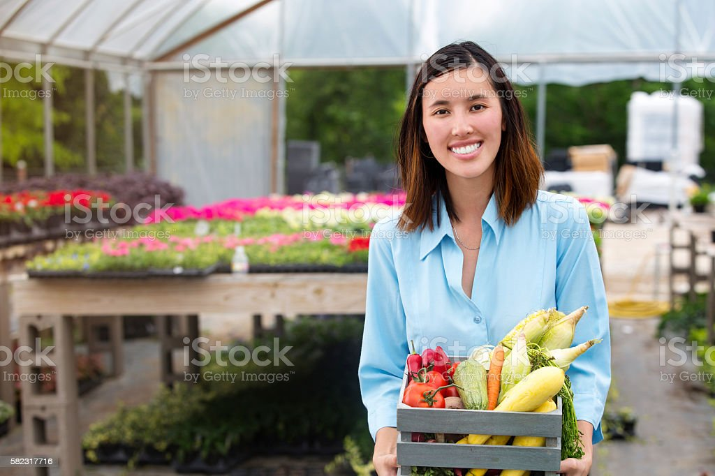 Woman purchases fresh veggies at farmer's market stock photo