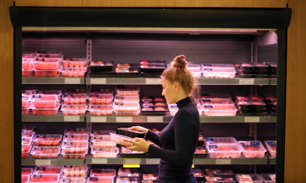 Woman purchasing a packet of meat at the supermarket Woman purchasing a packet of meat at the supermarket red meat stock pictures, royalty-free photos & images
