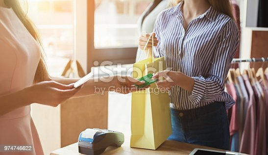 Woman paying with credit card for purchase at clothes showroom. Finance and non-cash transaction concept