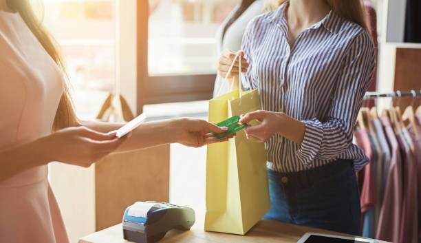 woman purchasing clothes with credit card - paying with card imagens e fotografias de stock