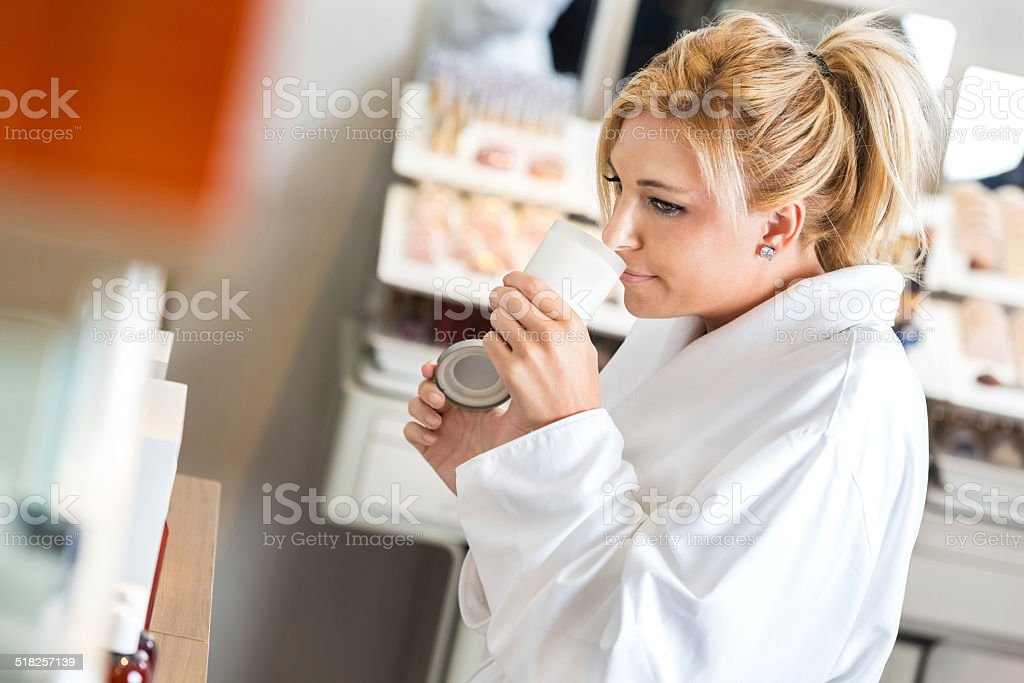 Woman purchasing scented candle during day at relaxing spa stock photo