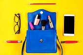 istock Woman purse, beauty products, smartphone, glasses on a bright yellow background, top view 692456032