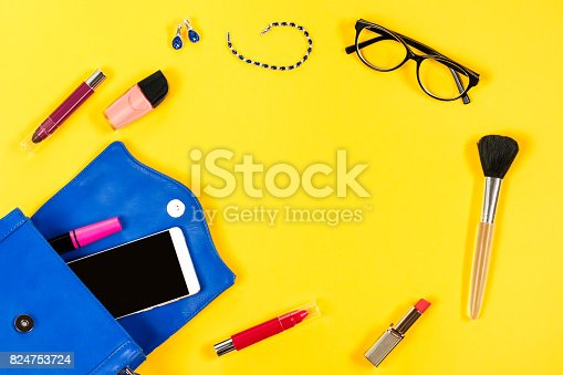 istock Woman purse, beauty products, smartphone, glasses on a bright yellow background, top view 824753724