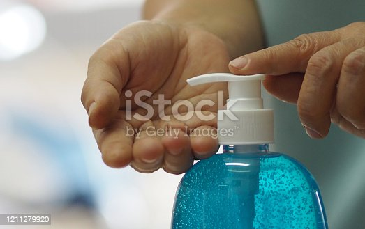 istock Woman push pump bottle use a hand wash gel to prevent germs protect virus covid 19 1211279920