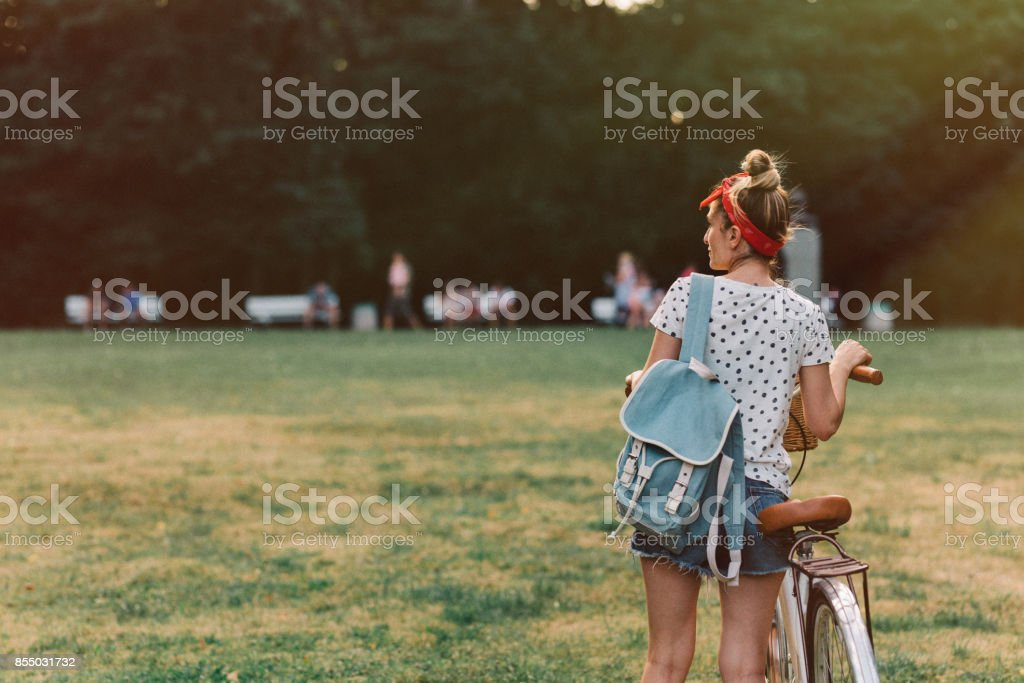 Woman pushing a bicycle in the park stock photo
