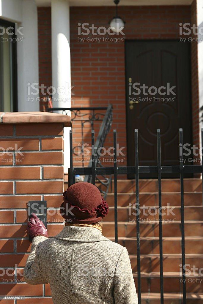 Woman pushing a doorbell royalty-free stock photo