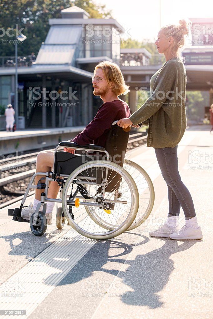 woman pushing a man in wheelchair at train station stock photo