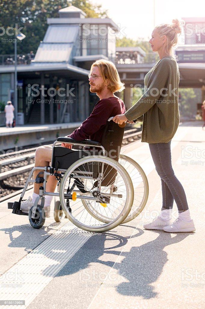 woman pushing a man in wheelchair at train station - foto de stock