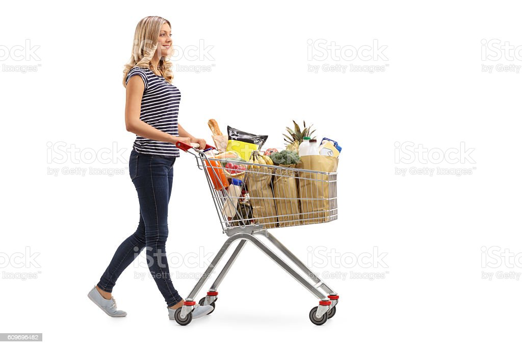 Woman pushing a shopping cart full of groceries stock photo