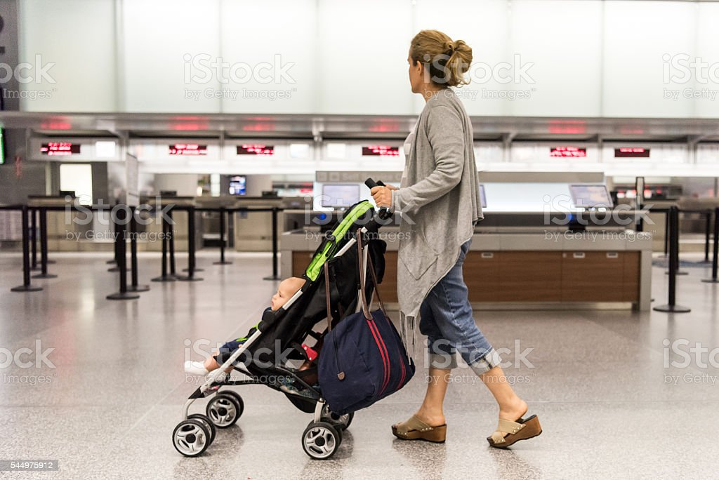 Woman pushing a stroller at the airport stock photo
