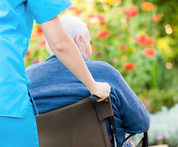 Eine Frau Schieben ein älterer Mann im Rollstuhl – Foto