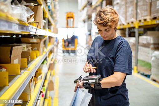 Woman in warehouse pushing buttons on wearable barcode reader