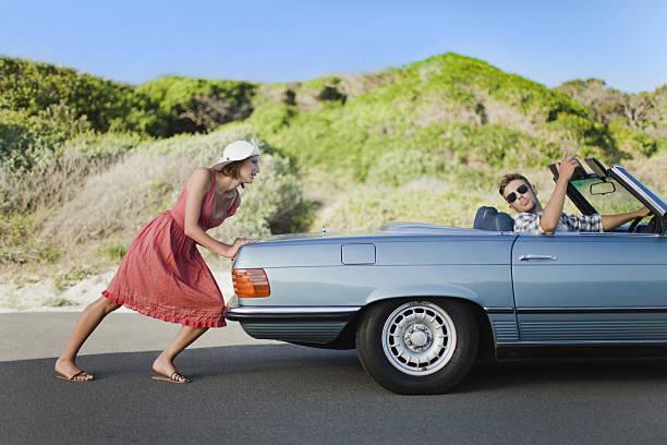 Woman pushing car as boyfriend steers stock photo