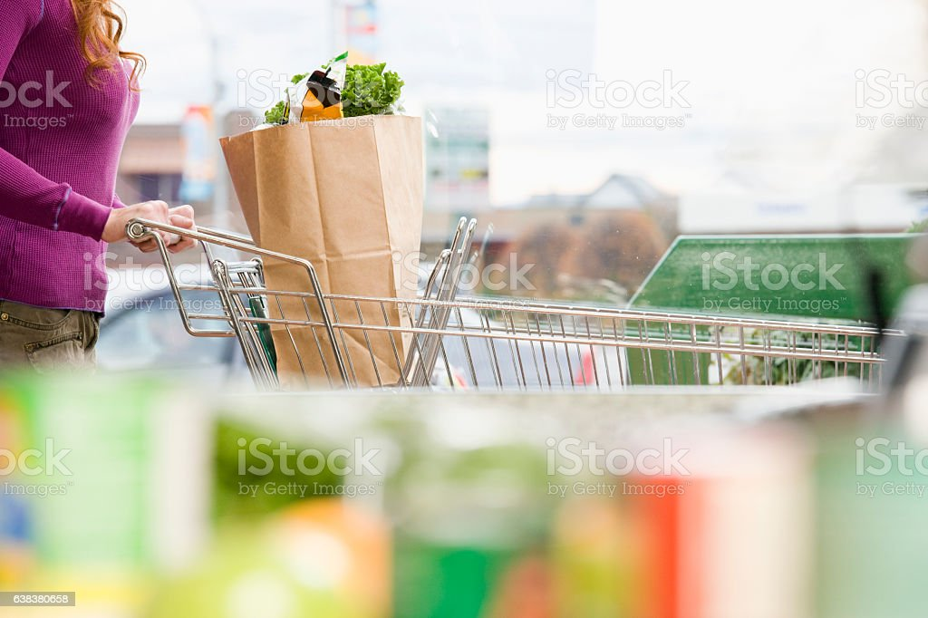 Woman pushing grocery cart in supermarket stock photo