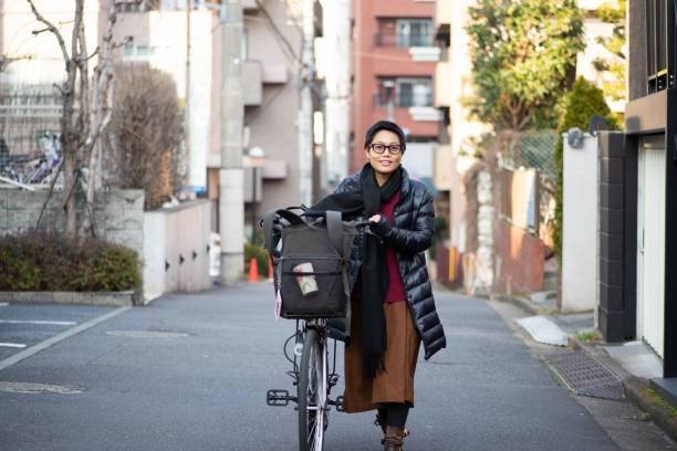 woman pushing her bike - showus стоковые фото и изображения