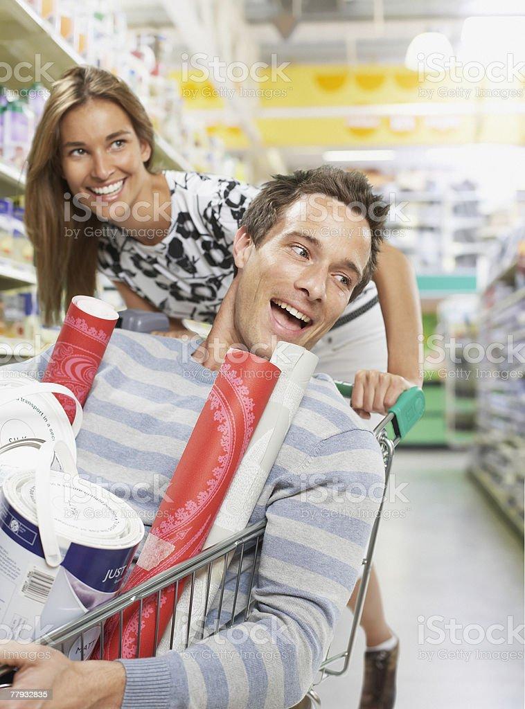 Woman pushing man in shopping cart