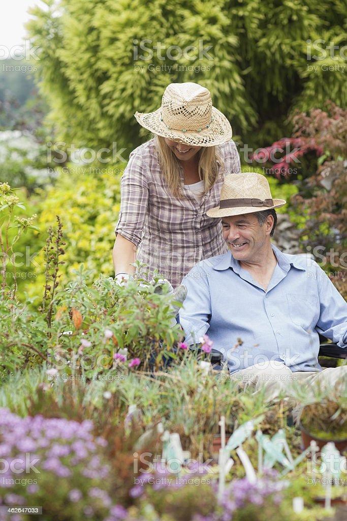 Woman pushing smiling man in wheelchair through garden wearing hats