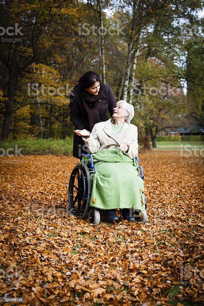 Woman pushing senior woman in wheelchair through autumn park royalty-free stock photo