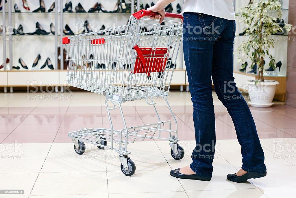 Woman pushing shopping cart in shoe store royalty-free stock photo