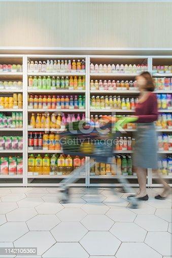 istock Woman pushing shopping cart in supermarket 1142105360