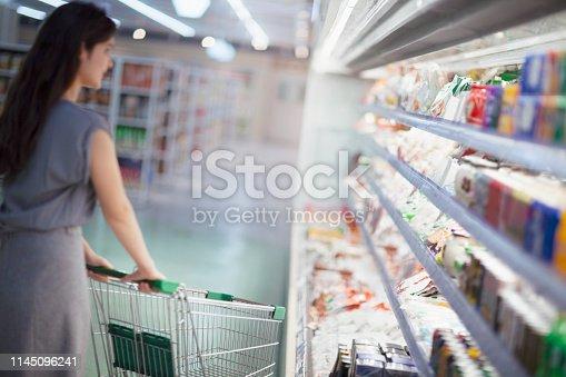 istock Woman pushing shopping cart in supermarket 1145096241