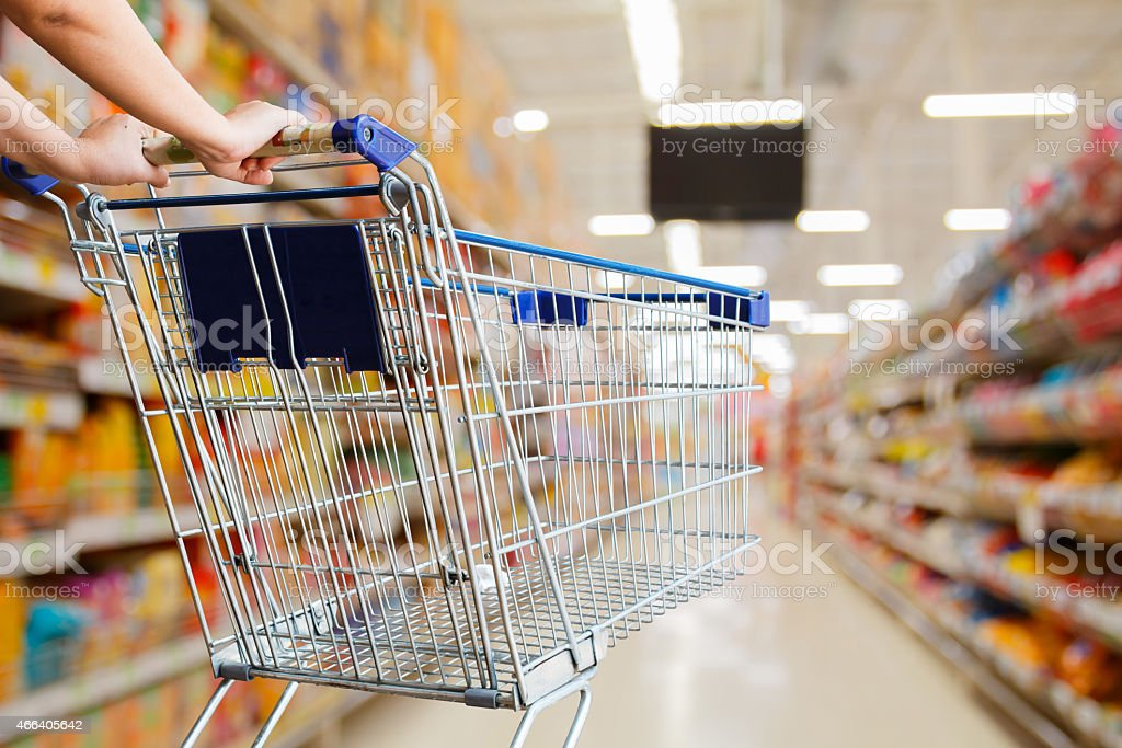 woman pushing shopping cart in supermarket stock photo
