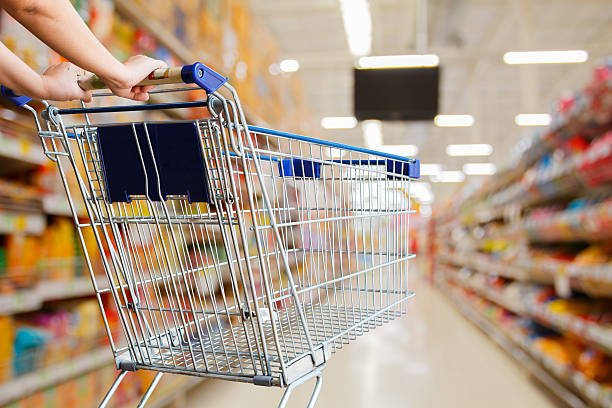 Mujer empujando la cesta de compras en el supermercado - foto de stock