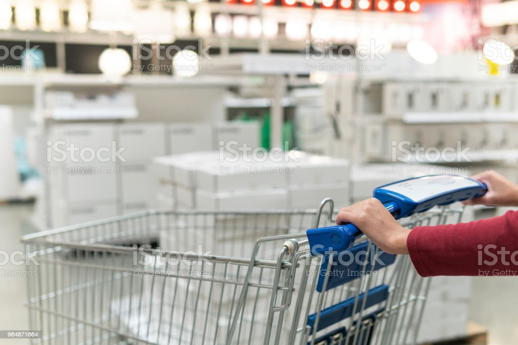 Woman pushing shopping cart in supermarket store abstract blur background with shopping cart, Supermarket aisle with empty shopping cart royalty-free stock photo