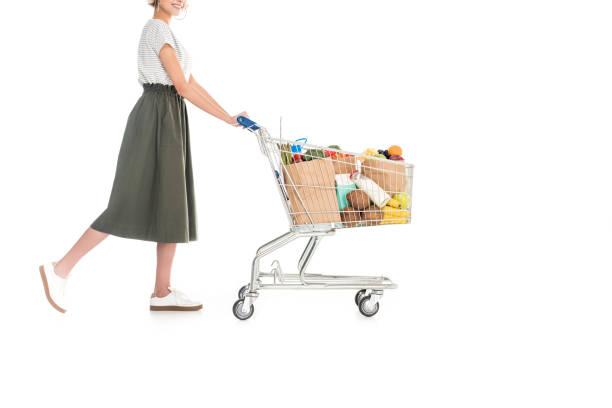 frau schieben einkaufswagen mit einkaufstüten - trolley kaufen stock-fotos und bilder