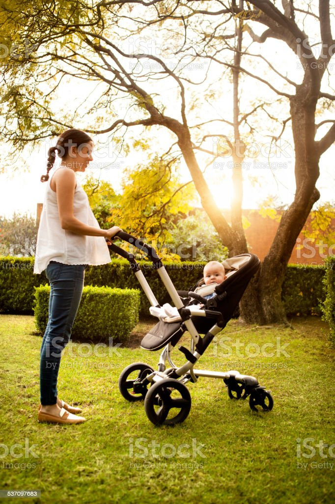 Woman pushing stroller with baby stock photo