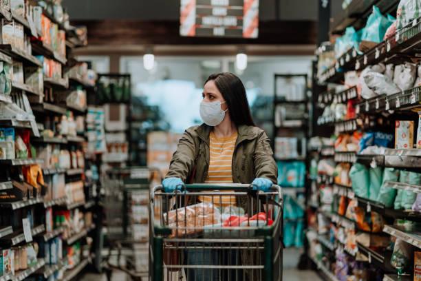 Woman pushing supermarket cart during COVID-19 stock photo