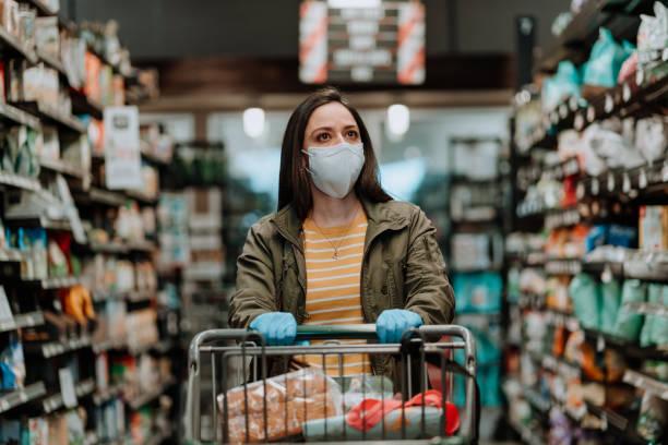 frau schiebt supermarktwagen während covid-19 - pandemie stock-fotos und bilder