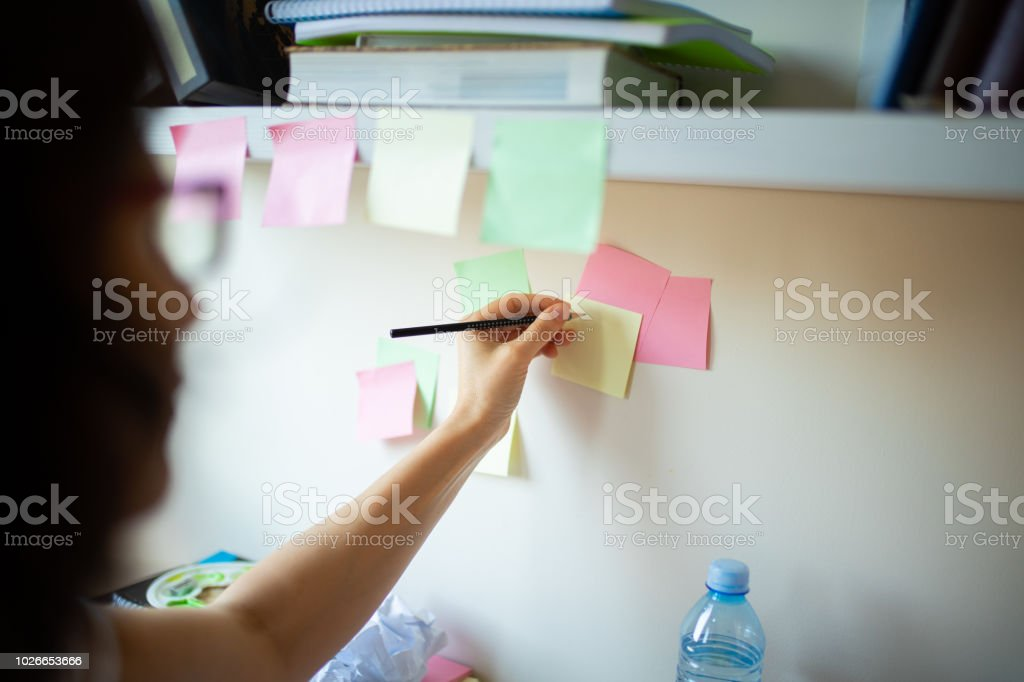 woman write on adhesive note on wall at home office