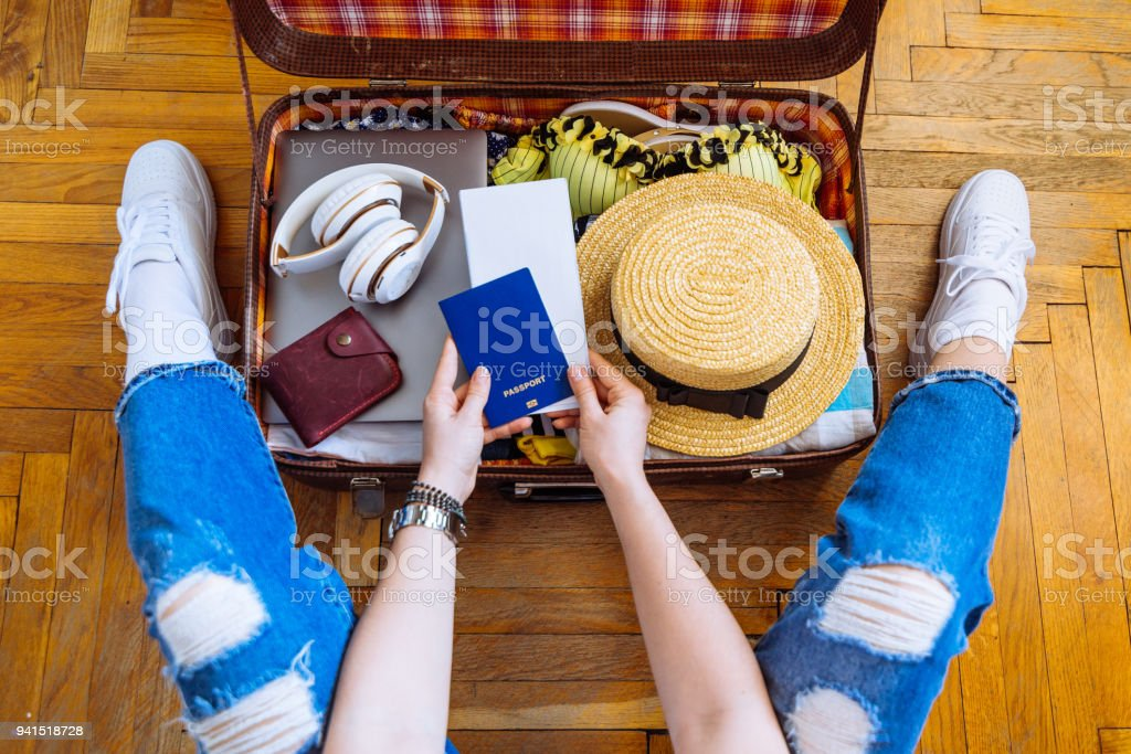 woman put clothes in suitcase while sit on floor. preparing for trip. travel concept stock photo