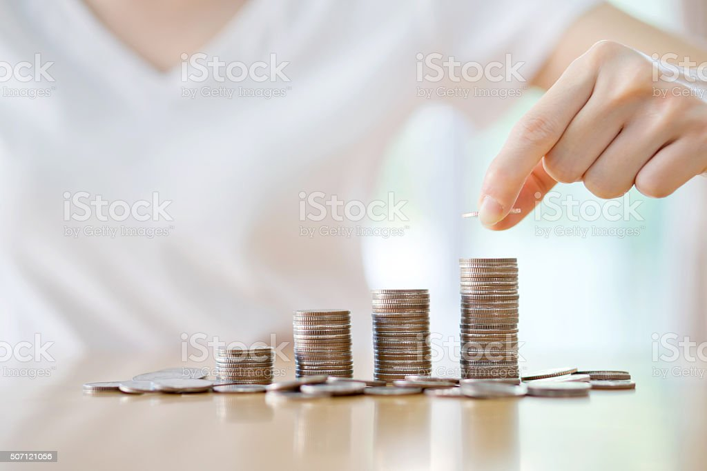 woman put coins to stack of coins stock photo