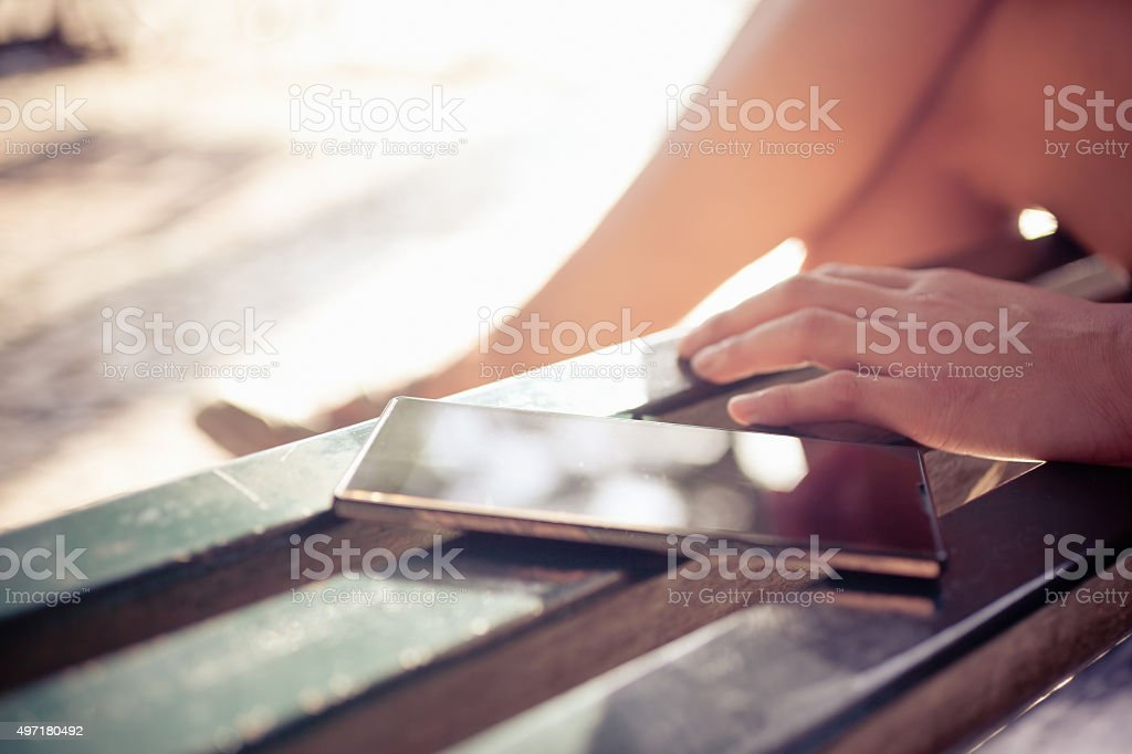 Woman Put Down Her Phone on Bench and Enjoying Outdoor stock photo